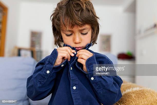 little boy buttoning his shirt - port photos et images de collection