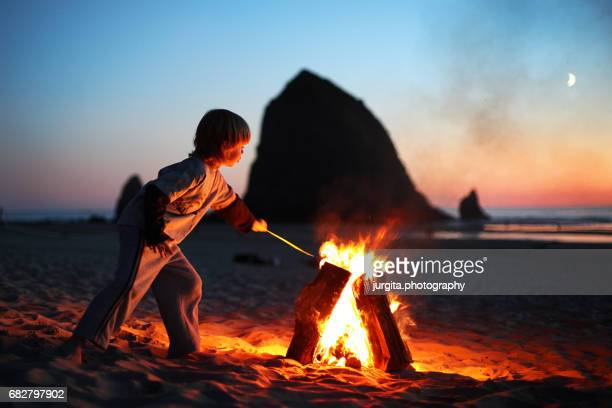 little boy by bonfire on the beach - utomhuseld bildbanksfoton och bilder