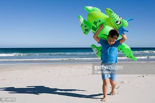 kleine junge tragen aufblasbarer drachen am strand - knaben in badehosen stock-fotos und bilder
