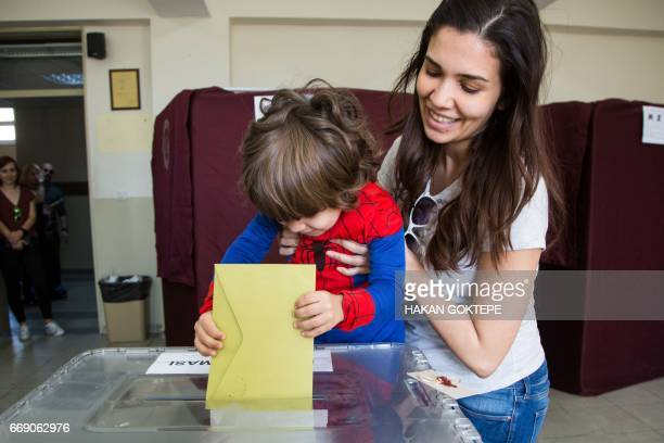 A little boy casts a ballot at a polling station during the referendum on expanding the powers of the Turkish president on April 16 2017 in the...