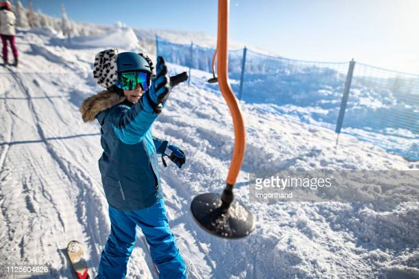 little boy catching a hanger on a platter ski lift. - ski lift stock pictures, royalty-free photos & images