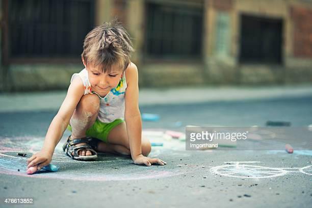 Little boy chalking on the street