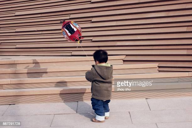 A little boy chasing balloons