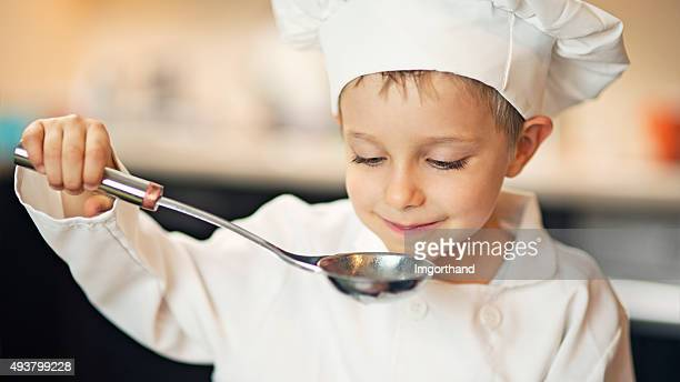 Little boy chef tasting soup.