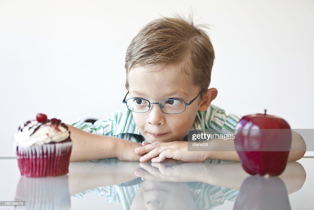 Little boy choosing between a cupcake and apple : Bildbanksbilder