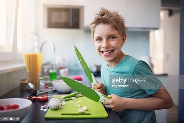 Little boy chopping garlic in kitchen