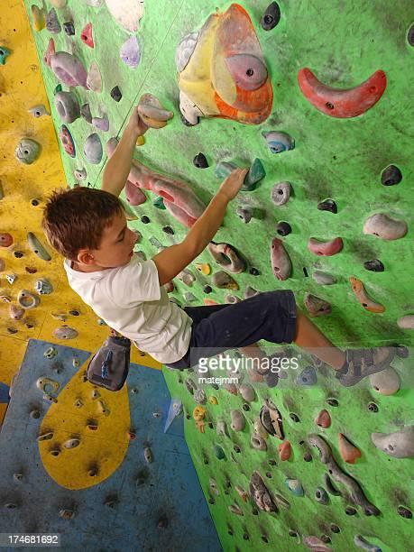 A little boy climbing a rock wall in a rock climbing center