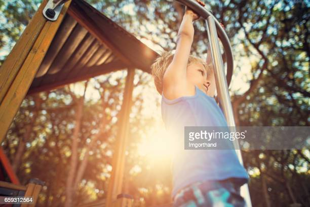 Little boy climbing in pine forest playground