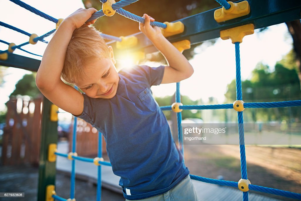 Little boy climbing on the playground : Stock Photo