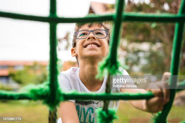 little boy climbing rope frame - playground stock pictures, royalty-free photos & images