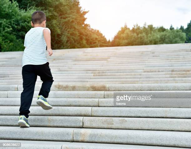 little boy climbing stairs outdoors - ténis calçado desportivo imagens e fotografias de stock