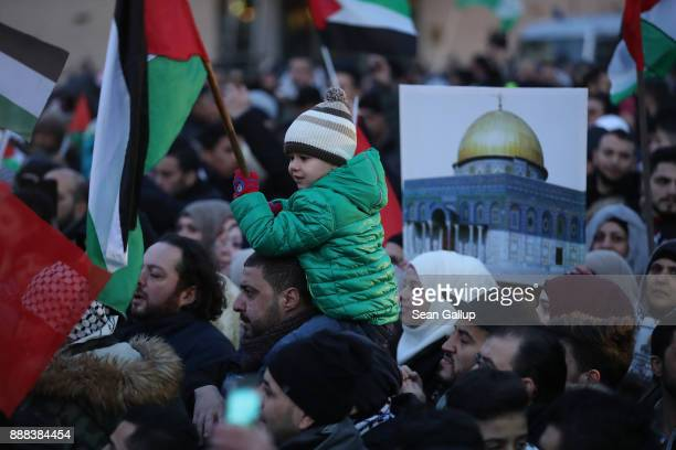 A little boy clutches a Palestinian flag as a demonstrator holds up a photograph of the AlAqsa mosque in Jerusalem among people who had gathered in...