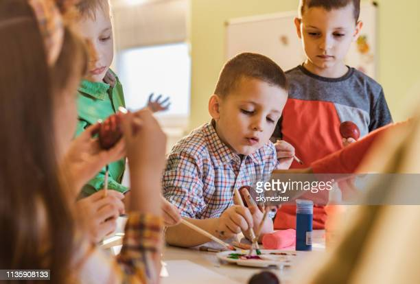 little boy coloring easter eggs with friends at preschool. - public celebratory event stock pictures, royalty-free photos & images