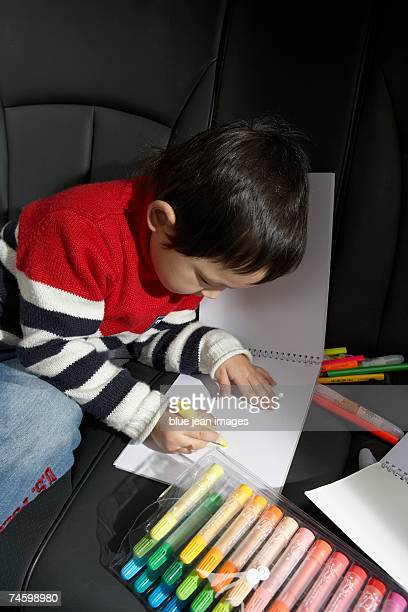 Little boy coloring in the back seat of a car