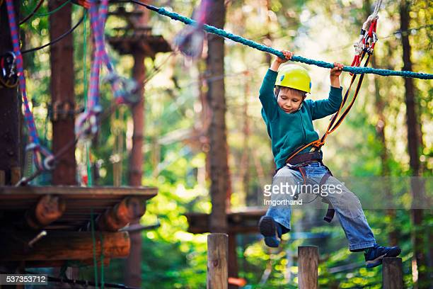 Little boy completing ropes course in outdoors adventure park