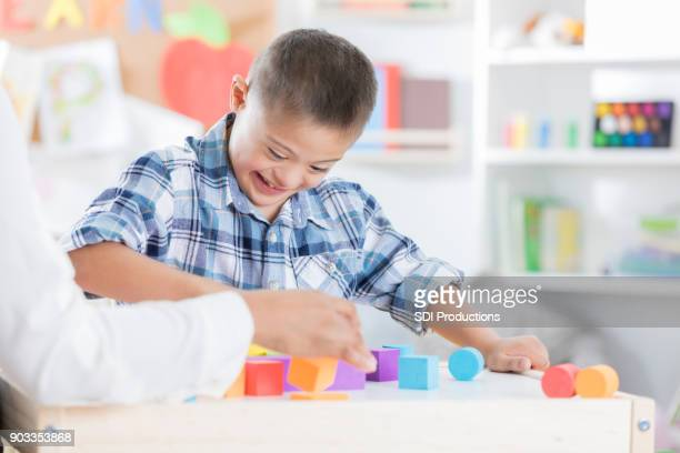 Little boy concentrates on building with wooden blocks