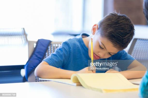 Little boy concentrates on drawing at school