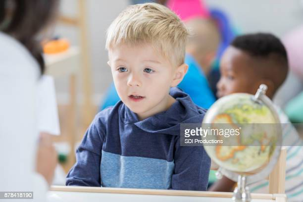 Kleiner Junge konzentriert sich beim Betrachten von Karteikarten