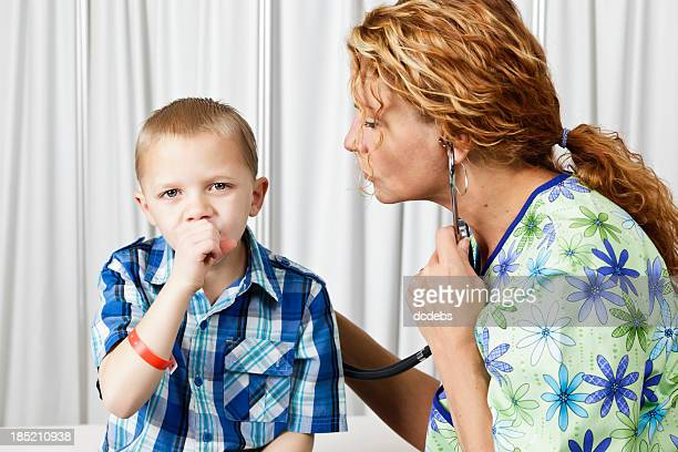A little boy coughing while a doctor checks his lungs