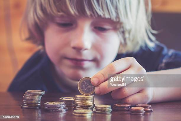little boy counting coins - 1 euro photos et images de collection
