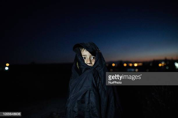 A little boy covered with a jacket out of the camp during a cold night A group of refugees outside in the field near Diavata refugee camp in...
