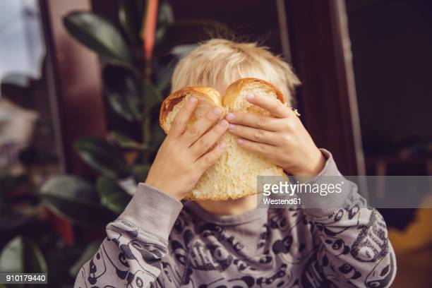 little boy covering his face with a slice of white bread - brot stock-fotos und bilder