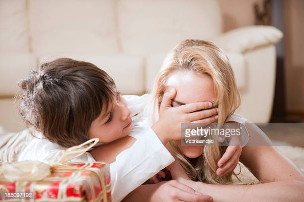Little boy covering his mothers eye to show her a gift