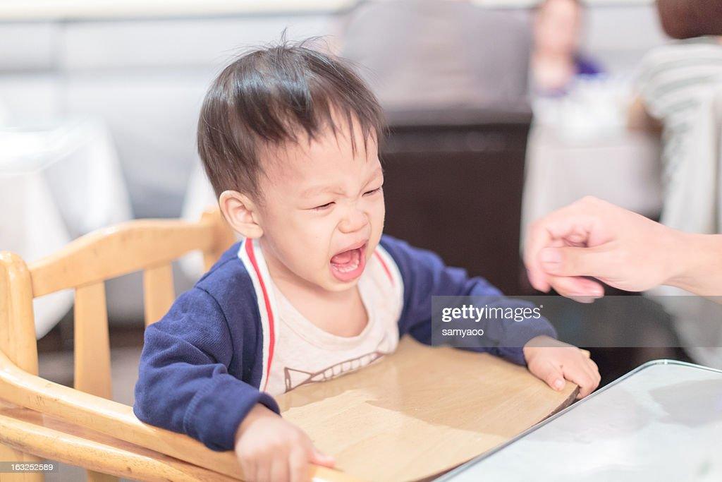 Little boy cries out on chair : Stock Photo