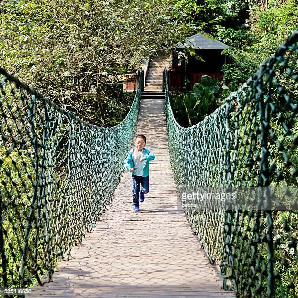 Little boy crossing the rope bridge