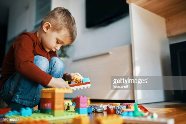 little boy crouching on the floor at home playing with building bricks - spielen stock-fotos und bilder