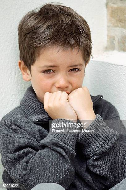 Little boy crying, hands over mouth, portrait