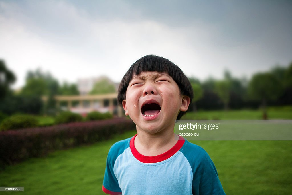 Little boy crying on grass : Stock Photo