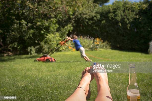 """little boy cutting grass while parent watches - """"danielle donders"""" stock pictures, royalty-free photos & images"""