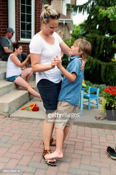 Niño bailando en los pies de la madre en familia.