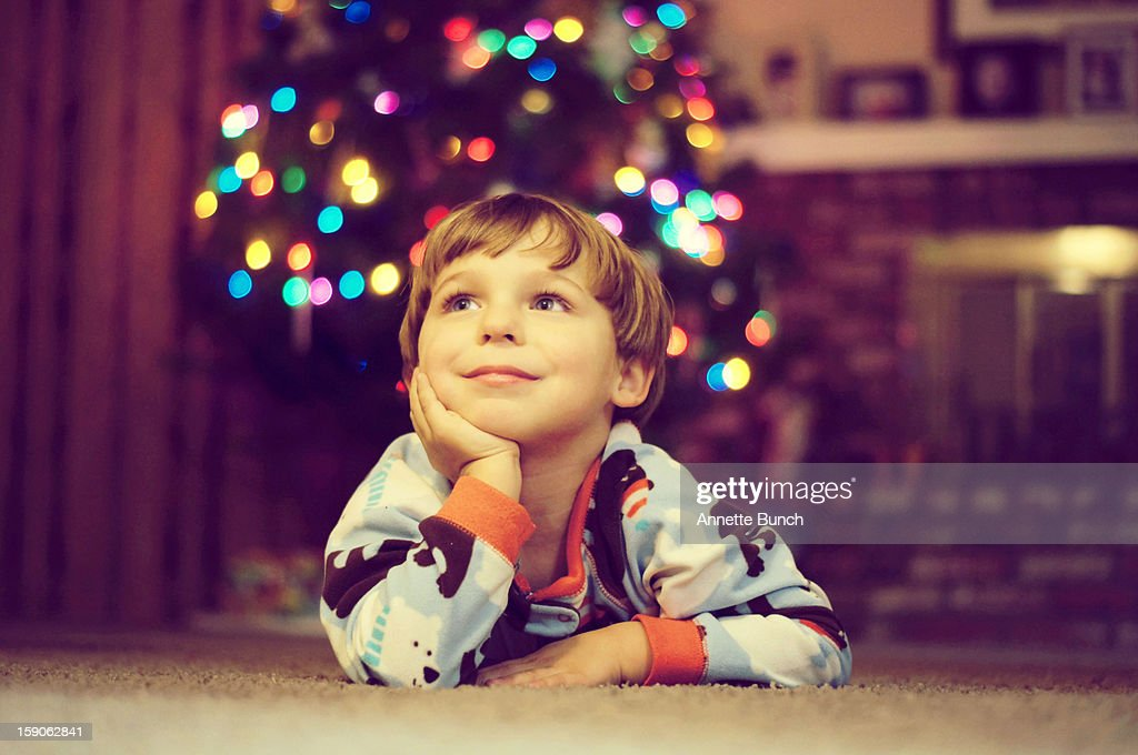 Little boy daydreaming next to Christmas tree : Stock Photo