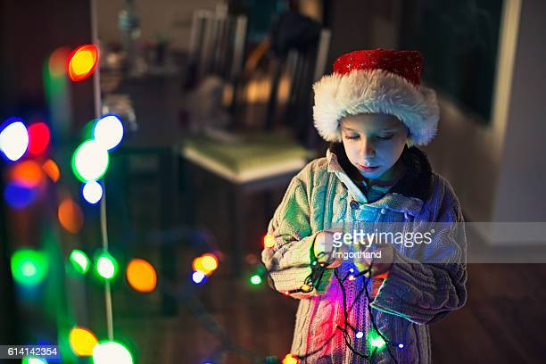 Little boy decorating room with christmas lights