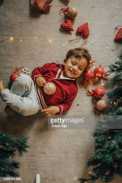 little boy decorating the christmas tree. - children only stock pictures, royalty-free photos & images