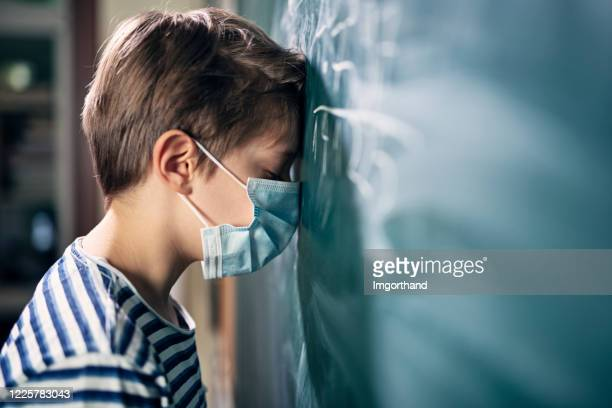 kleiner junge von der schule während covid-19 pandemie depressiv. - schulkind nur jungen stock-fotos und bilder