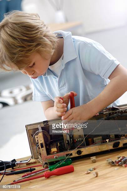 Little boy disassembling an old radio