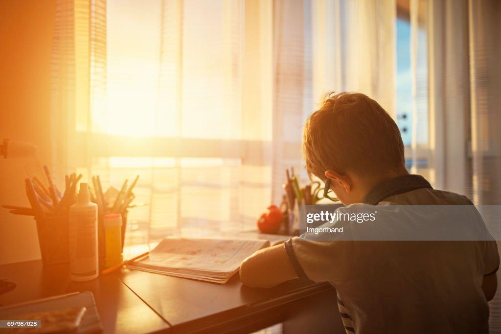 Little boy doing homework at home : Stock Photo
