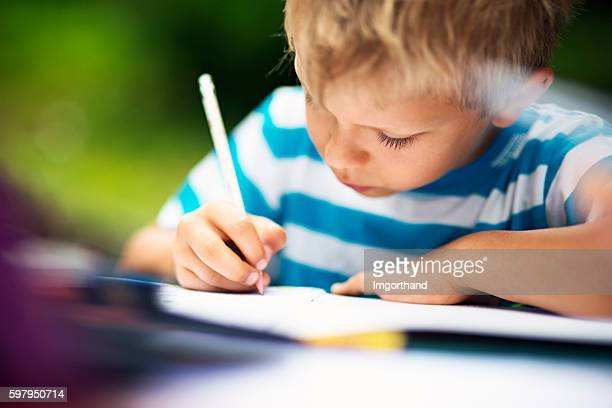 Little boy doing homework in the garden