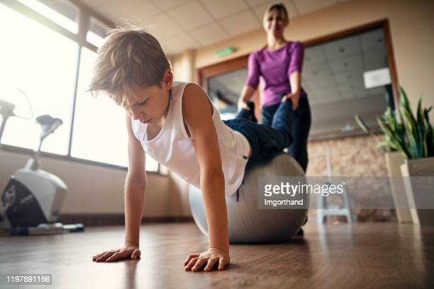 little boy doing physical therapy exercises - physical therapy stock pictures, royalty-free photos & images