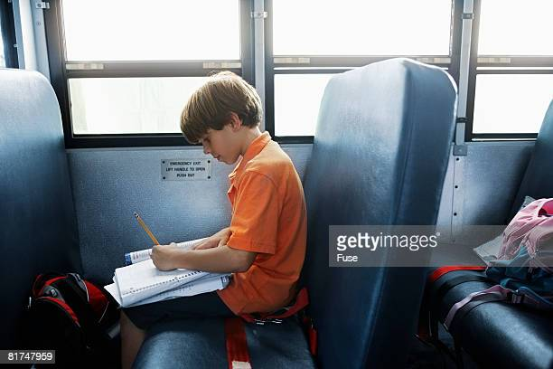 little boy doing schoolwork on a school bus - one boy only stock pictures, royalty-free photos & images