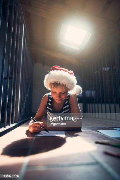 Little boy drawing a letter to santa