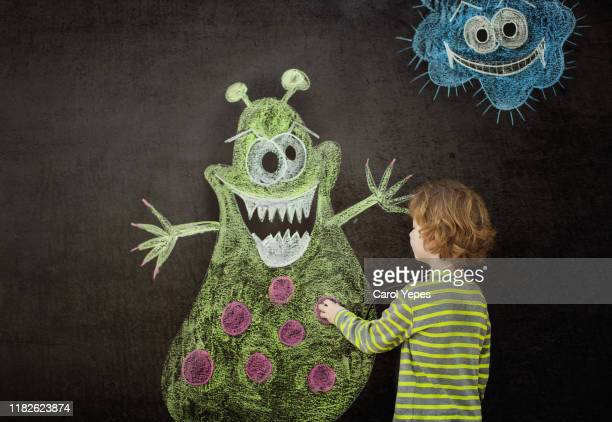 little boy drawing a virus on chalkboard - micro organism stock pictures, royalty-free photos & images