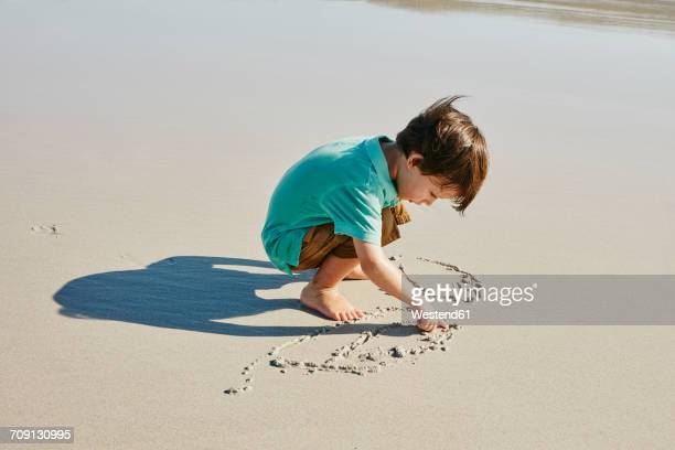 Little boy drawing in the sand on the beach