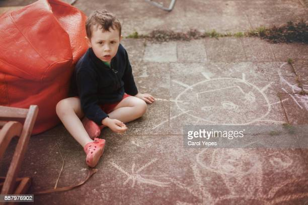 little boy (3) drawing  with chalk on the floor outdoors
