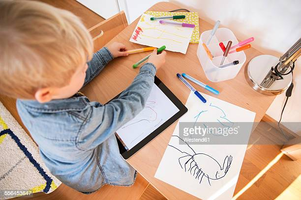 Little boy drawing with digital tablet
