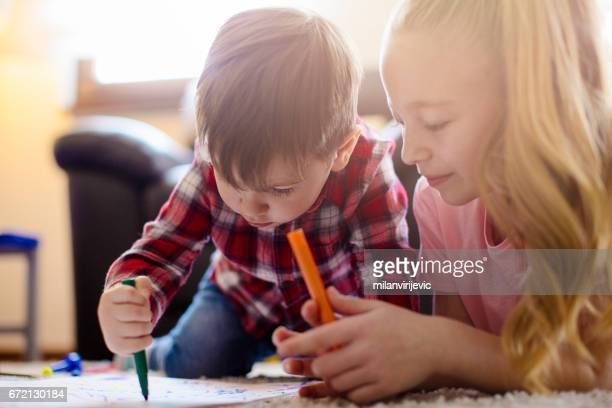 Little boy drawing with his sister