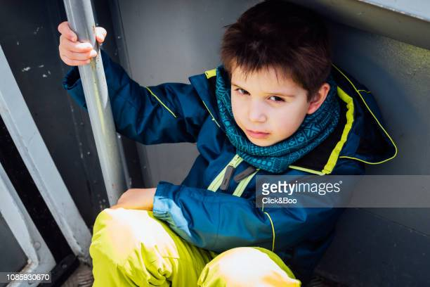 Little boy dressed in ski clothes inside a cabin cableway
